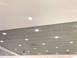 White color emulsion painted gypsum ceiling and Macro grid ceiling combined as False ceiling interiors for an commercial retail shop building and LED lights fixed for lighting