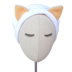 White color handmade headband with cat ears as decoration made out of fur fabric texture placed on mannequin head with beautiful eyelashes. This hair band is great as skincare headband.