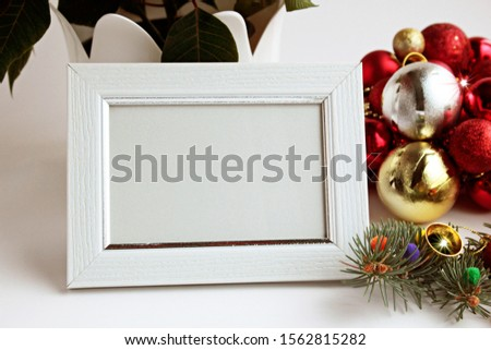 White color,wooden empty picture frame stand in front of christmas ball and poinsettia flower.