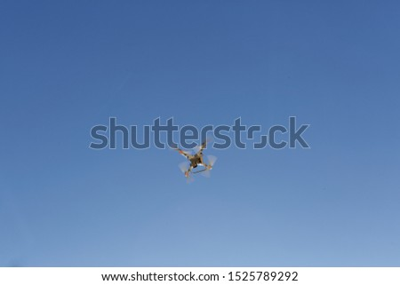 White colored aerial unmanned vehicle with camera flying over clear blue sky on a sunny summer day. View from ground.