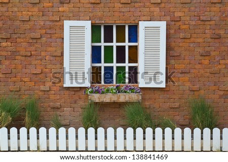 White colored glass windows, red brick walls, grass and wooden fence.