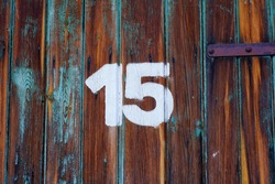 White colour number fifteen on an old abandoned brown colour wooden gate