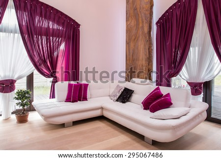 White comfortable corner sofa and rose cushions