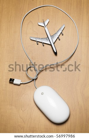 White computer mouse and a toy airplane on a wood tabletop