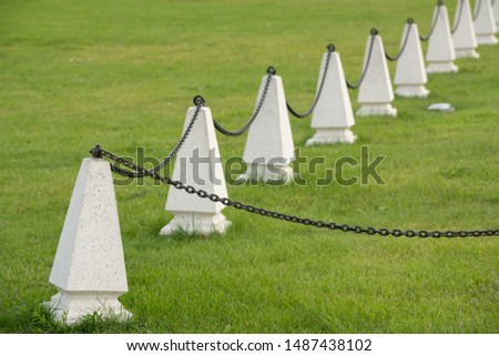 white concrete pillars with black chain. Fencing of the protected object in the Park #1487438102