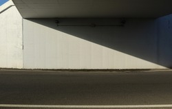 White concrete wall under an underpass divided in two obliquely by a shadow. Asphalt road in front. Background for copy space.