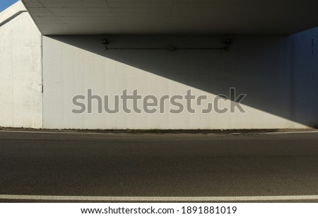 White concrete wall under an underpass divided in two obliquely by a shadow. Asphalt road in front. Background for copy space. Foto stock ©