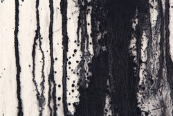 White concrete wall with black paint drips, drops and stains. Abstract background, rough grunge texture, dirty and messy old urban wall surface.