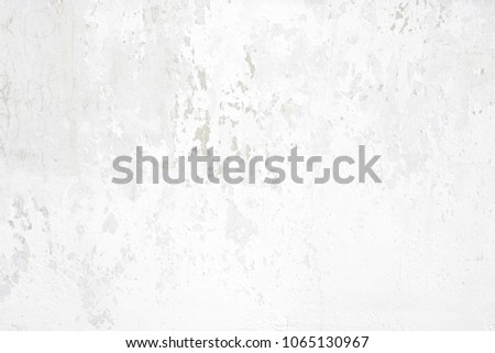 White concrete wall with small cracks and shabby plaster on surface