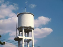 White concrete water tank on the tower: large outdoor public water storage tanks for water supply in villages or communities in the city On the sky background with copy space.