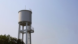 White concrete water tank on the tower. large outdoor public water storage tanks for water supply in villages or communities in the city On the sky background with copy space. Selective focus