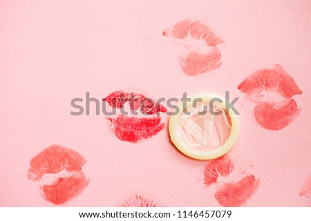 white condom isolated and lipstick kisses on pink background, safe sex, love affair #1146457079