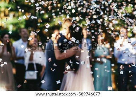 White confetti falls over wedding couple dancing on the porch #589746077