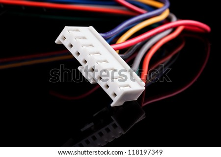 White connector with multicolored wires on a black background.