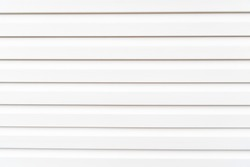 White construction vinyl siding panels. House covered with plastic vinyl siding. Vinyl siding wall surface with horizontal lines