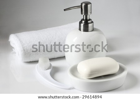 White container with liquid soap, bar of soap, towel and brush on light background.