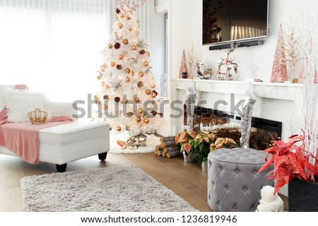White contemporary Christmas tree. A plush loveseat sofa in the foreground with pink accents.  #1236819946