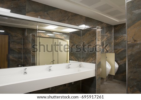 White Corian Sink, Chrome Tap, Wooden Doors and Dark Green Marble Textured Wall Tiles at Commercial Public Male Bathroom at Office Building #695917261