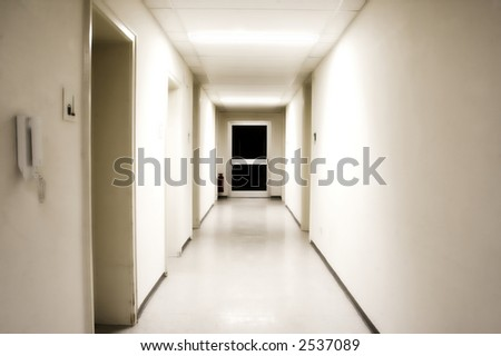White corridor with black door at the end