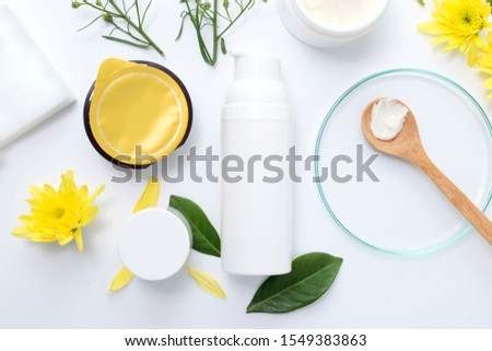 White cosmetic bottle with clay mask  wooden spoon yellow flowers and serum skincare cream products on white background. Aerial view #1549383863