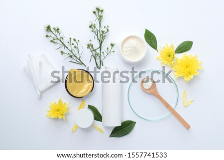 White cosmetic bottle with clay mask wooden spoon yellow flowers and serum skincare cream products on white background. Aerial view #1557741533