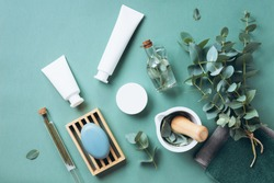 White cosmetic bottles, eucalyptus flowers, towels, soap on green background. Top view, flat lay. Natural organic beauty product concept. Spa, skin care, body treatment.