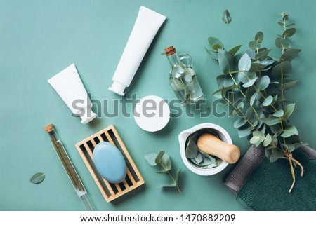 White cosmetic bottles, eucalyptus flowers, towels, soap on green background. Top view, flat lay. Natural organic beauty product concept. Spa, skin care, body treatment. ストックフォト ©