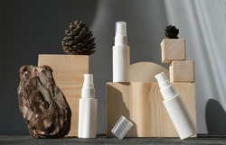 white cosmetic bottles on wooden podium. pedestal or display for advertizing. variety of pine cones and pine bark. geometric podium. Scene with geometrical forms. eco friendly design