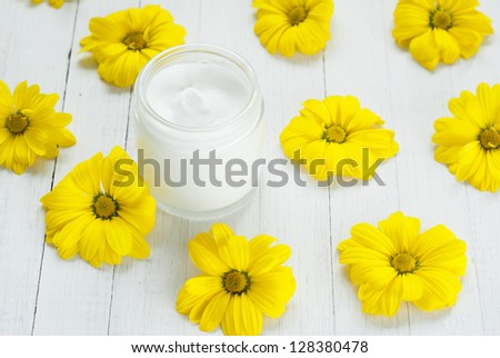 white cosmetic cream with yellow flowers on wooden