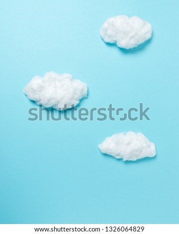 White cotton clouds on pastel blue background. Minimal concept.