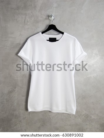 Shutterstock White cotton t-shirt textile hanging center grey empty background. Clear label space for business message.