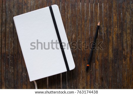White cover notebook with black pencil on rustic wooden table flat lay photo. Closed notebook with blank cover flat lay photo. Notepad on table top view. Sketchbook banner template. Art logo mockup
