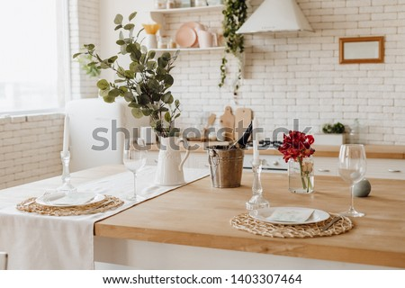 White Cozy Kitchen Table at Home Provence Interior. Champagne Bottle in Ice Bucket for Homey Dinner Date on Light Wooden Counter. Cozy Traditional Desk on Modern Brick Wall Background