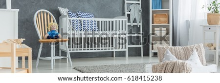 White cradle with patterned pillows in cozy baby boy bedroom #618415238