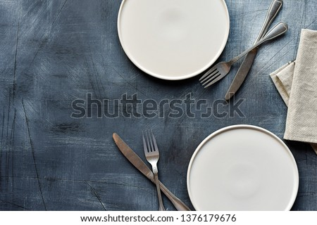 White craft plate, cutlery and napkin on dark stone table. Top view, copy space, Table setting. background for menu, layout, place for text , recipe background