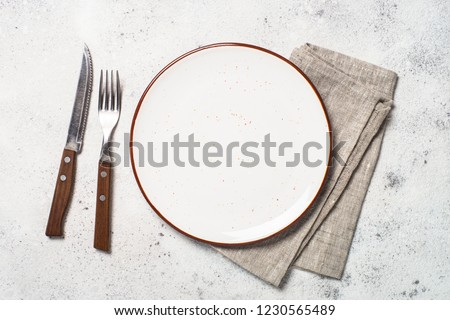 White craft plate, cutlery and napkin on white stone table. Top view, copy space.
