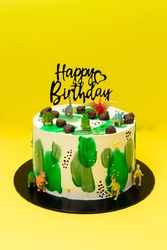 White cream cake, decorated with dinosaur figurines in Jurassic period jungle; on yellow background. A selective focus photo of dinosaur figurine on top of the cake. A birthday cake concept photo.