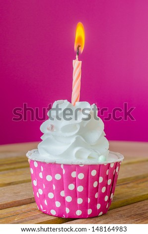 White cream cupcake with candle