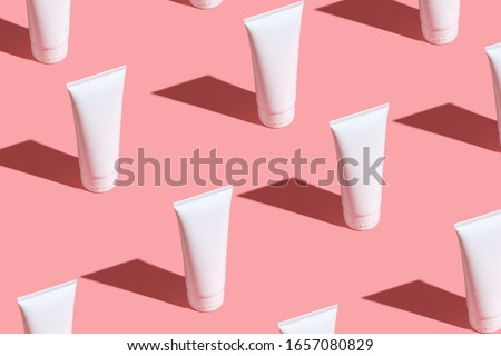 White cream tubes on light pink table. Care about face, hands, legs and body skin. Women beauty products. Cosmetic pattern. Empty place for logo on tubes. Hard light directly flat lay.