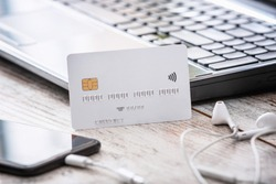 White credit or debit payment card mockup.Empty banking card on the working desk, next to mobile phone and laptop.