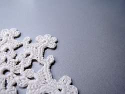 White crocheted doily on a gray background close-up