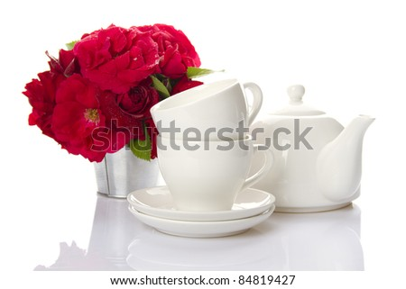 White crockery for tea kettle, two cups and saucers and a bouquet of red roses in a small iron bucket