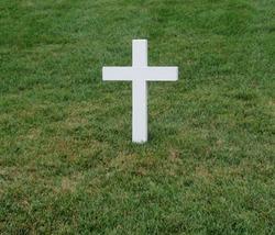 White cross grave maker standing alone in Arlington National Cemetery