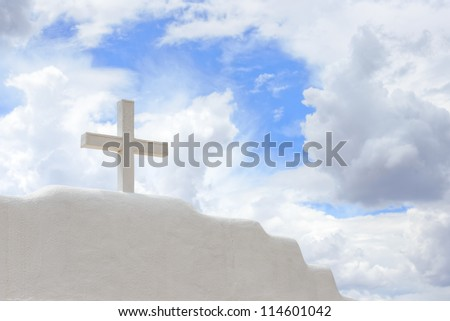 White Cross of mission church stands against thunderclouds sky