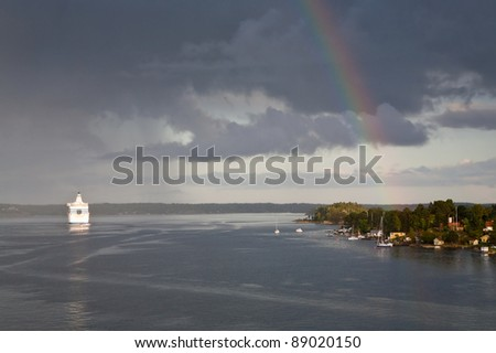 white cruise liner and rainbow in rain during sunshine in Baltic sea