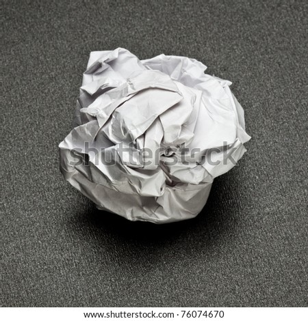 white crumpled paper on a gray table, the failure of unsuccessful project
