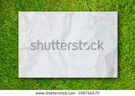White Crumpled paper on Green grass background