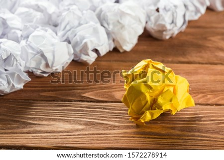 White crumpled up piece of paper on wooden table as idea #1572278914
