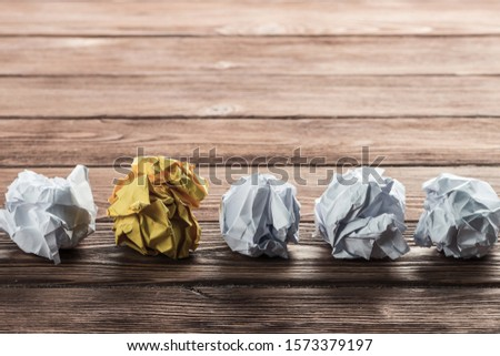 White crumpled up piece of paper on wooden table as idea #1573379197