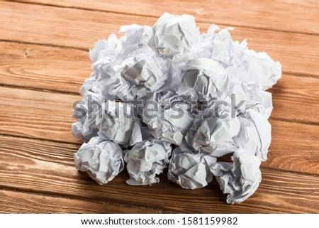 White crumpled up piece of paper on wooden table as idea #1581159982